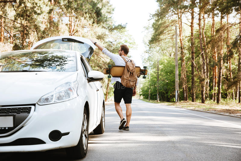 Man with skateboard outdoors standing near car. Looking aside. royalty free stock images