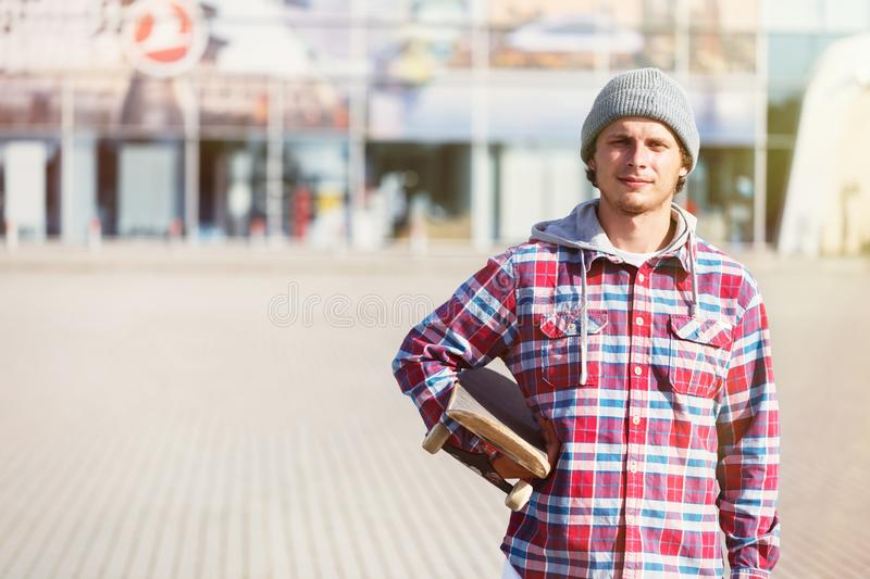 Man with Skateboard. Portrait of hipster man dressed in cheked shirt and cap holding skateboard before modern building royalty free stock images