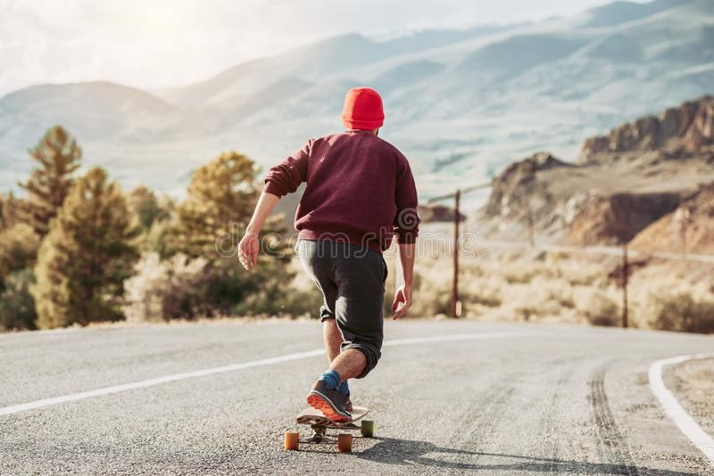 Man skateboarding at mountain road stock photography