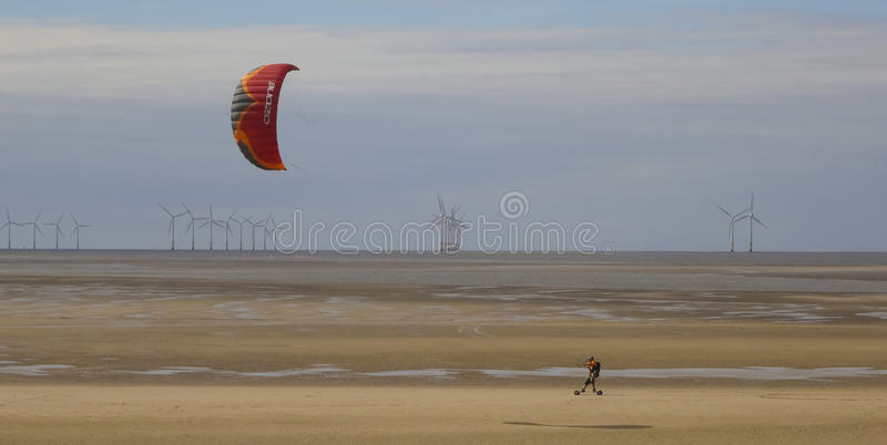 A Man Skateboards with a Parasail Near Wallasey. WALLASEY, ENGLAND, JULY 3. A tidal flat on July 3, 2016, near Wallasey, England. A man skateboards across the royalty free stock photos