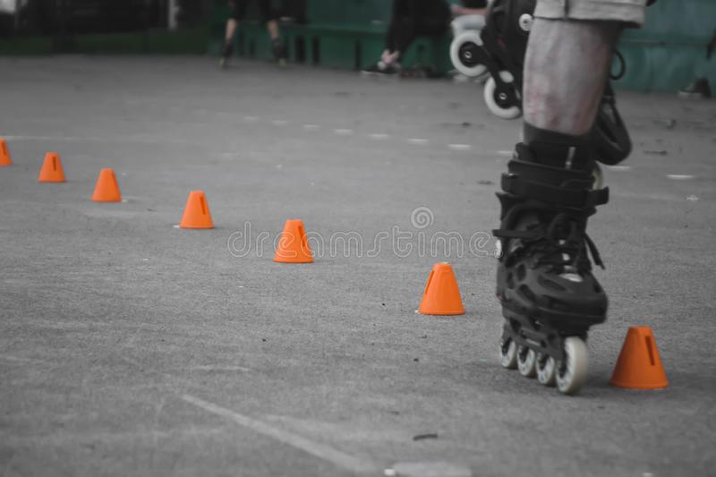 man skates on asphalt and goes round cones royalty free stock images