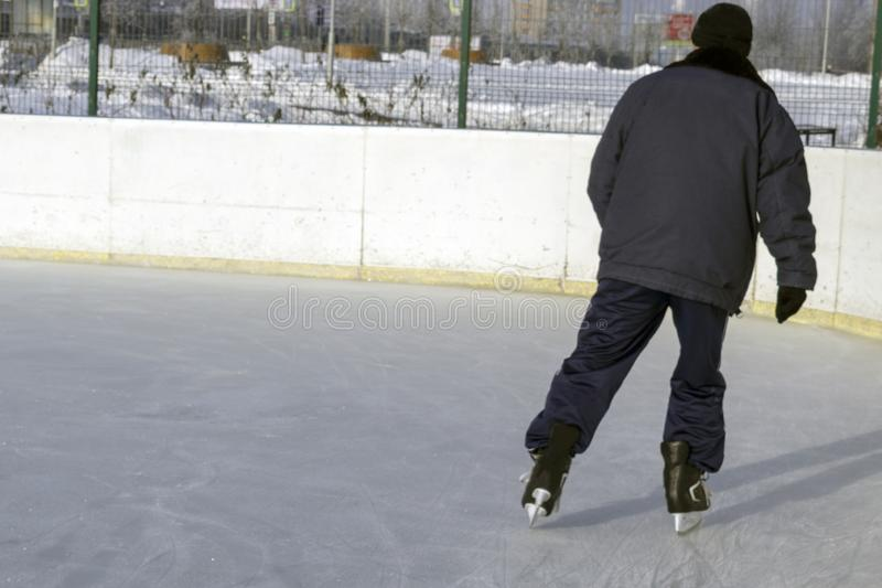 A man skates on a city skating rink. A man in black clothes with his back to us skating on a city skating rink royalty free stock photo