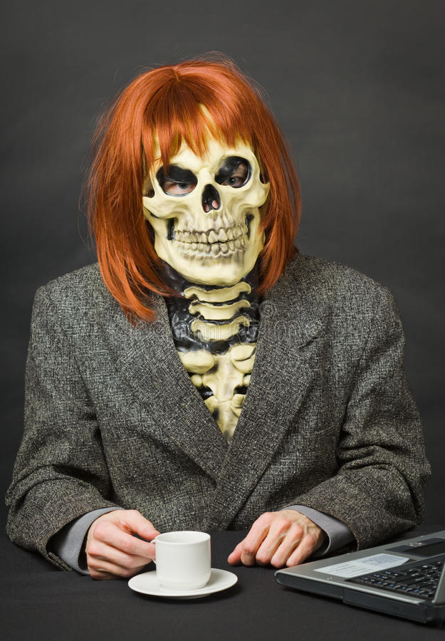 Man - skeleton with red hair drinking coffee stock image