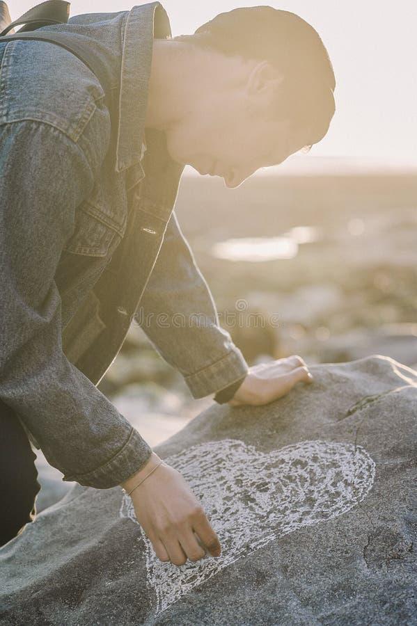 Man Sketching Heart on a Gray Rock stock photos