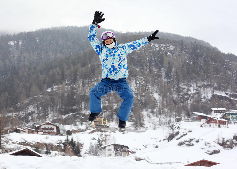 Man in ski helmet jumps on mountain royalty free stock image