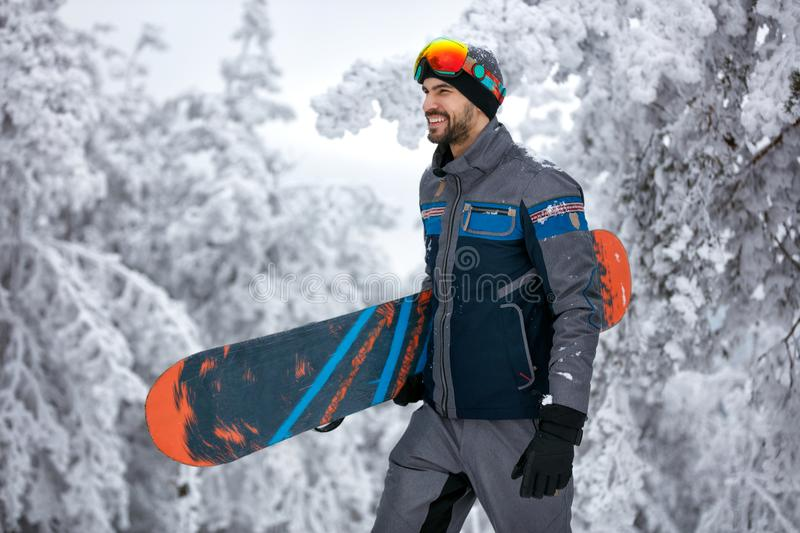 Man with ski mask holding his snowboard, extreme sport and winter holiday. On the mountain stock photo