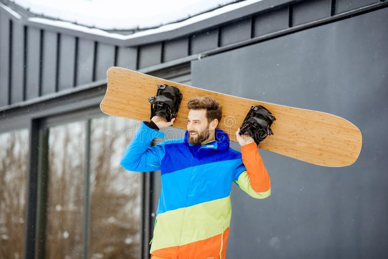 Man in ski suit near the house in the mountains royalty free stock image