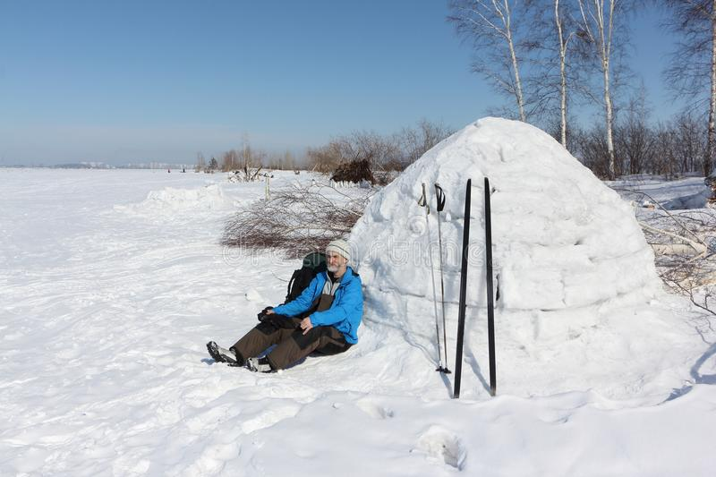 Man skier sitting by an igloo on a glade. In the winter royalty free stock photo
