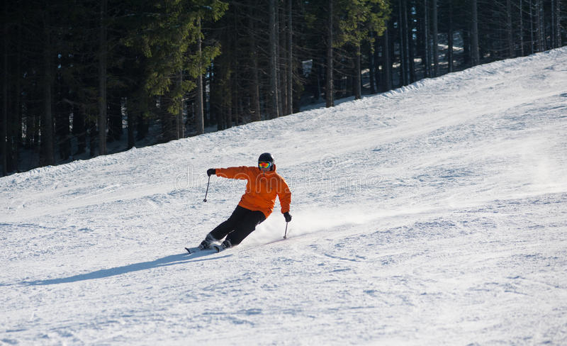 Man skier skiing downhill at ski resort. Against forest. Male is wearing orange jacket, helmet and goggles. Carpathian Mountains, Bukovel royalty free stock image