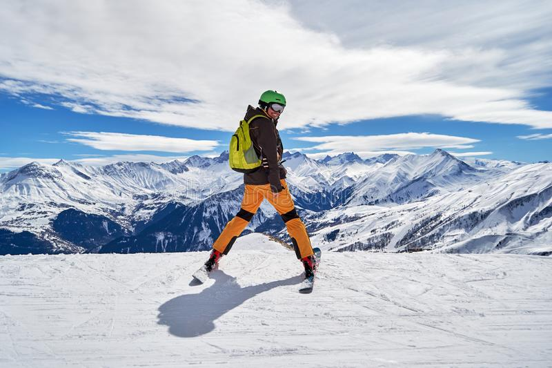Man skier smiling and posing with a beautiful winter mountain panorama in Les Sybelles ski domain, France, on a sunny day. Man skier smiling and posing with a stock image