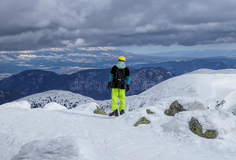 A man skier standing on the edge of mountain and looking down to the valley and try find good freeride. High tatras in clouds. stock images
