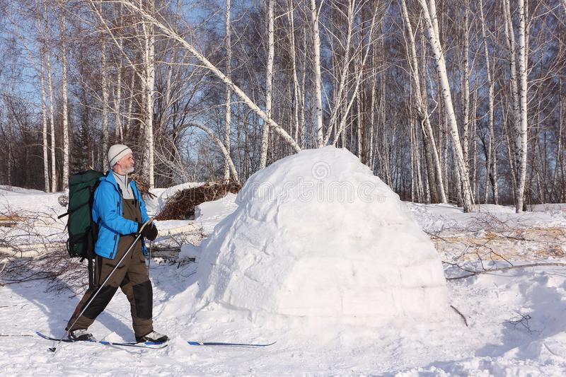 Man skier standing by an igloo on a glade. In the winter stock photo