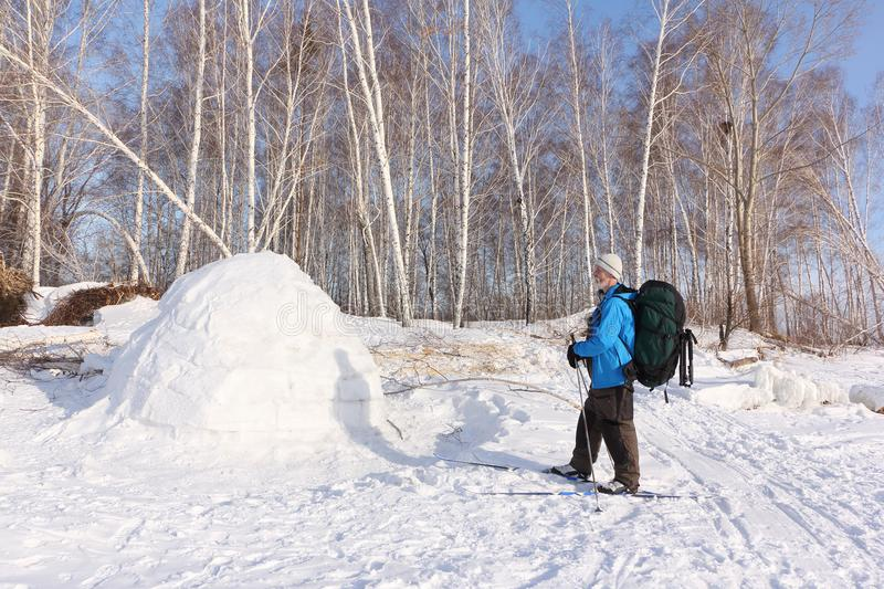 Man skier standing by an igloo on a glade stock images