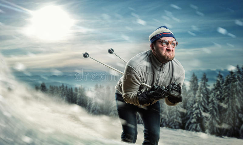 Man skiing. Bearded vintage skier in glasses skiing fast while snowing stock image