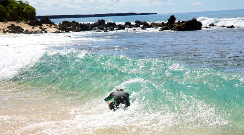 A man skimboarding at Big Beach in Maui stock photo