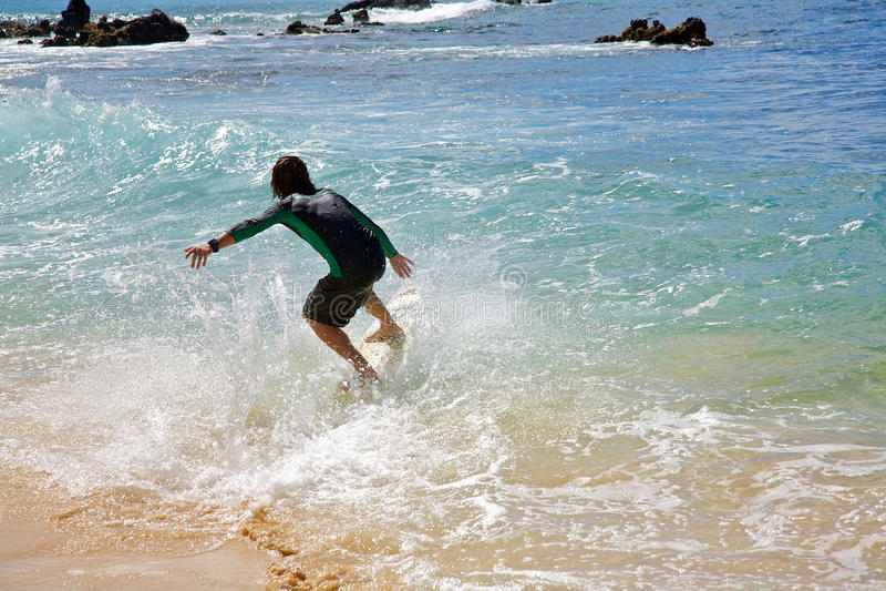 A man skimboarding at Big Beach in Maui royalty free stock photo