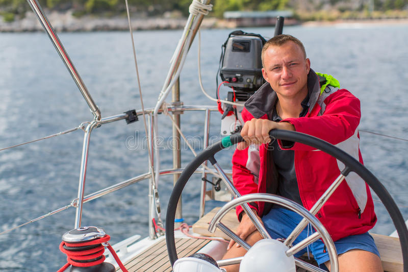 Man skipper steers boat sailing yacht on the sea. Sport. stock photo