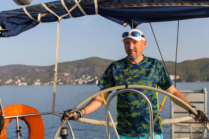 Man skipper steers wheel the sailing yacht boat. royalty free stock image