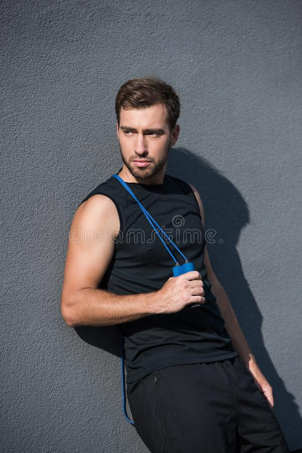 Young athletic man posing with skipping rope stock images