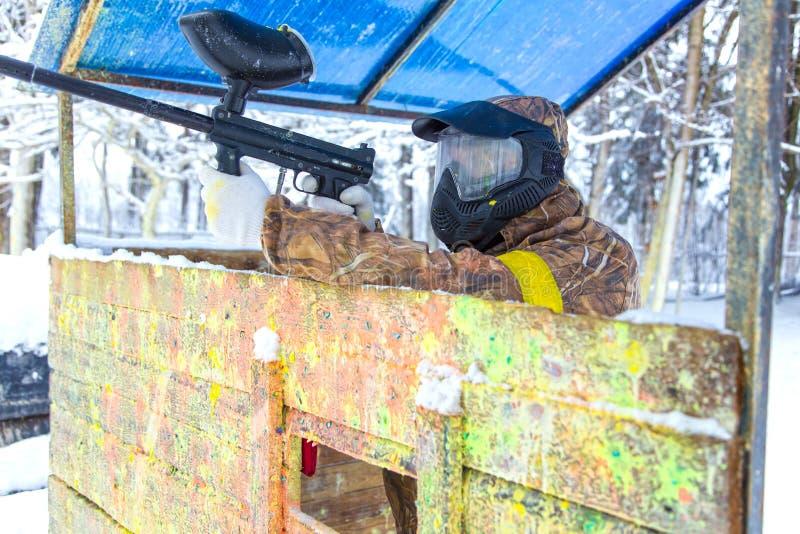 Man skytte från paintballvapnet bak träbefästning arkivbilder