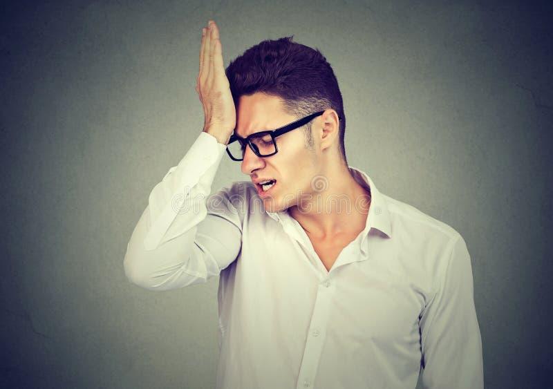 Man, slapping hand on head having regrets royalty free stock image