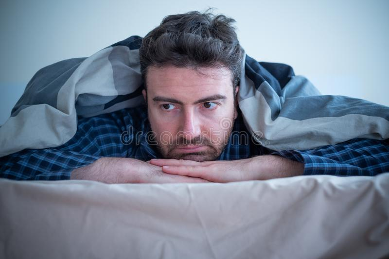 Man with sleep problem in his bed at home stock photography