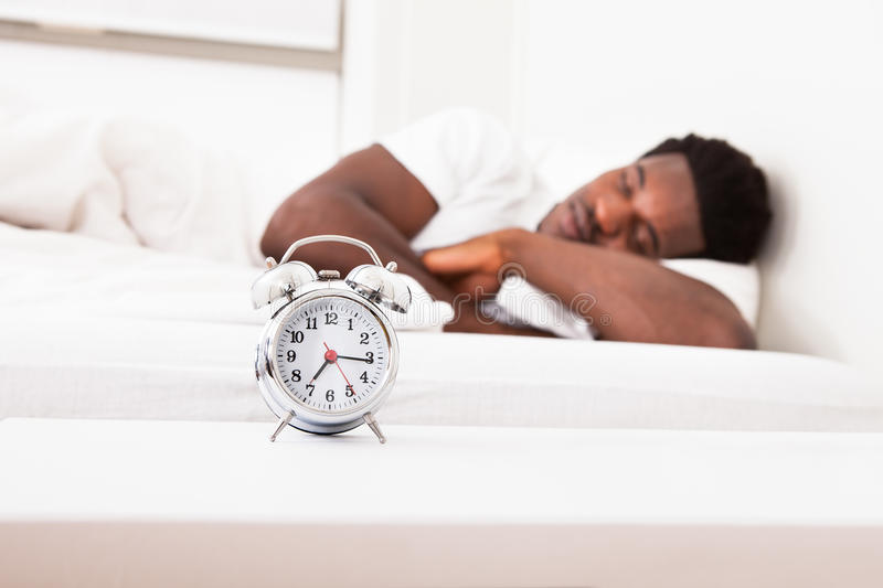 A man is sleeping with an alarm clock stock photography
