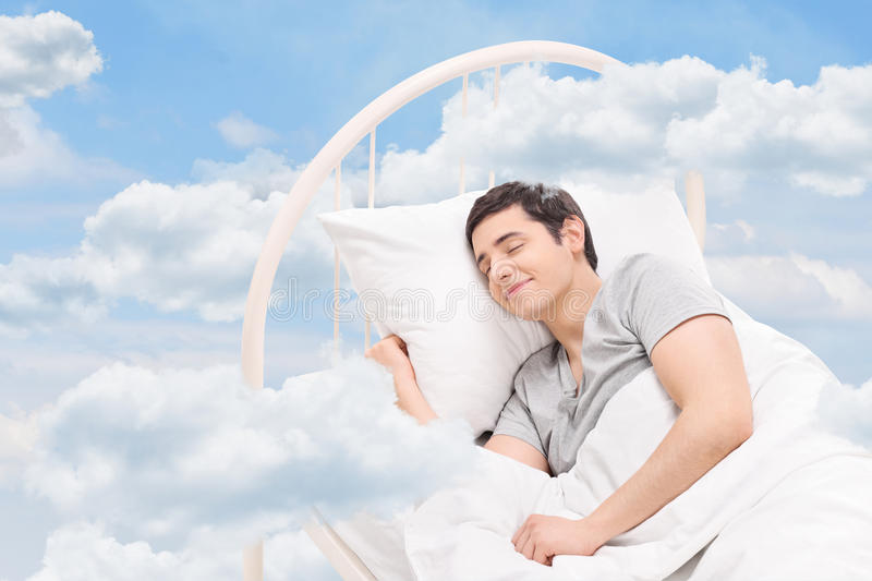 Man sleeping on a bed in the clouds stock photo