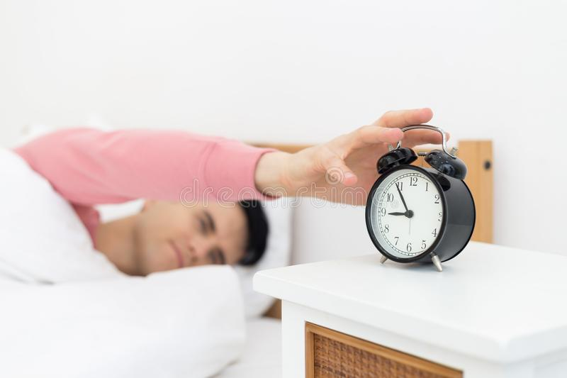 Man sleeping in bed early wake up not getting enough sleep. Feel irritated when they hear the alarm clock stock image
