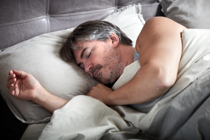 Man sleeping in bed. stock image