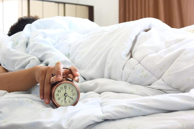 Man sleeping in the bedroom with Handle the alarm clock in the morning, Health concept stock photos