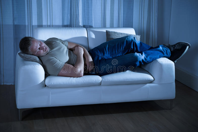 Man sleeping on couch. Portrait Of A Young Man Sleeping On Couch stock photos