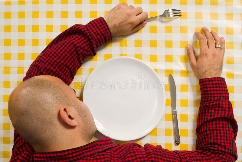 Man sleeping at the dinner table stock photos