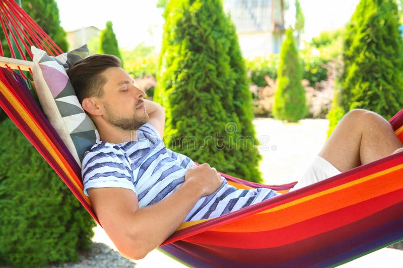 Man sleeping in hammock outdoors. On warm summer day royalty free stock images