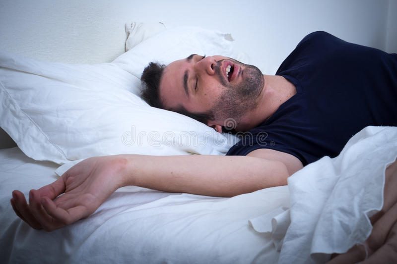 Man sleeping in his bed and snoring stock photo
