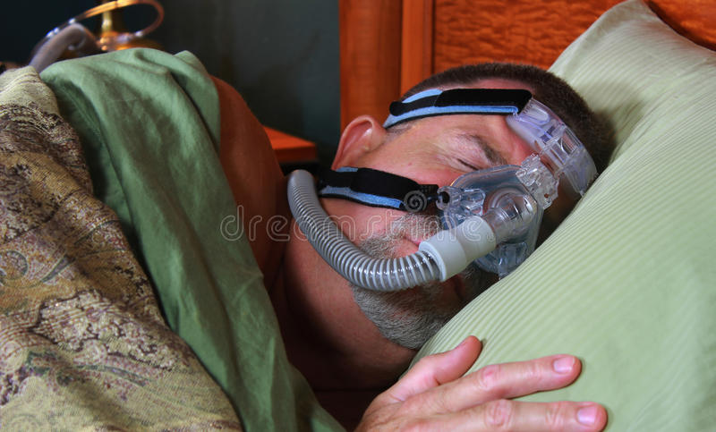 Man Sleeping Peacefully with CPAP. A man is sleeping peacefully with his CPAP (continuous positive airway pressure) mask. Front of mask is visible royalty free stock image