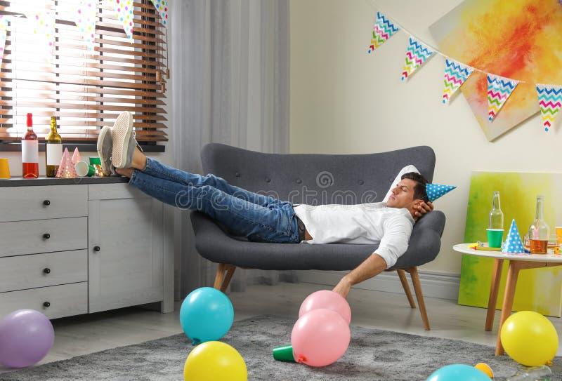 Man sleeping on sofa in messy room royalty free stock photos
