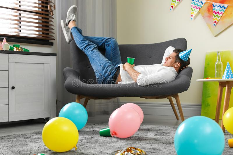 Man sleeping on sofa in room after party. Man sleeping on sofa in messy room after party royalty free stock photography