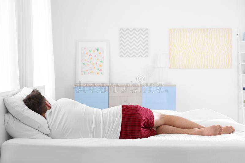 Man sleeping on two pillows at home stock photography