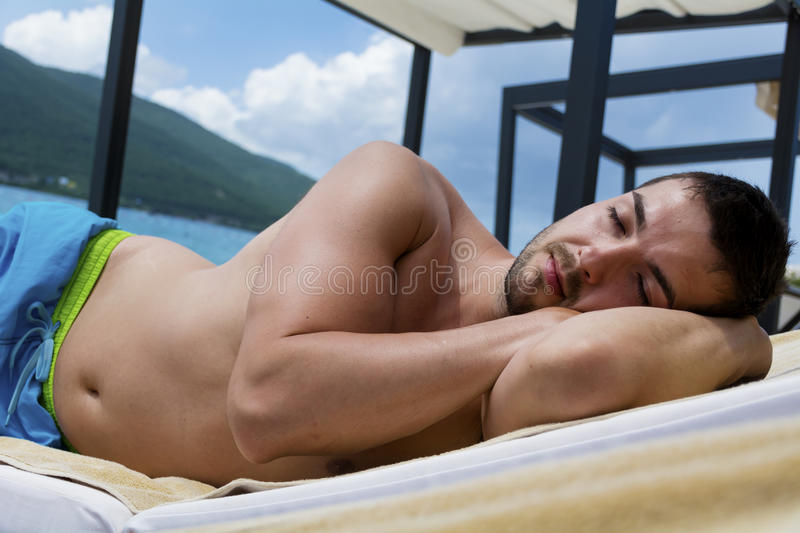 Man sleeping on a white sunbed on the beach royalty free stock photography