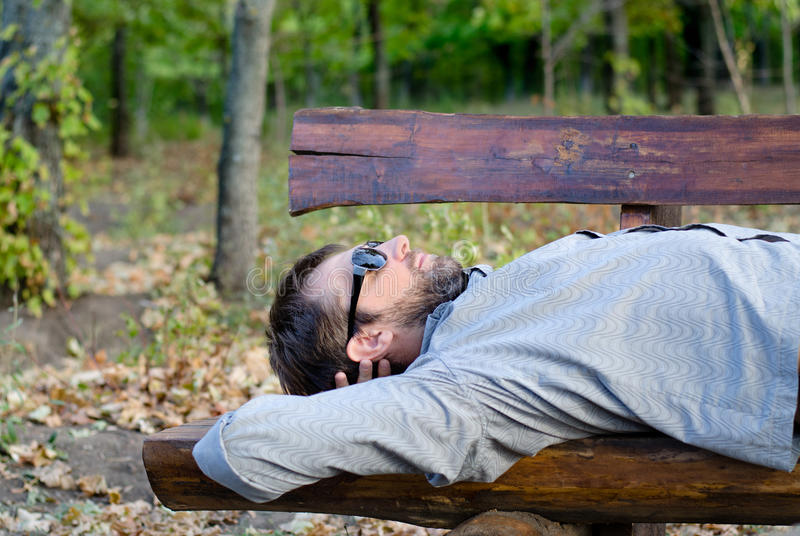 Download Man Sleeping On A Wooden Bench Stock Photo - Image: 27785130