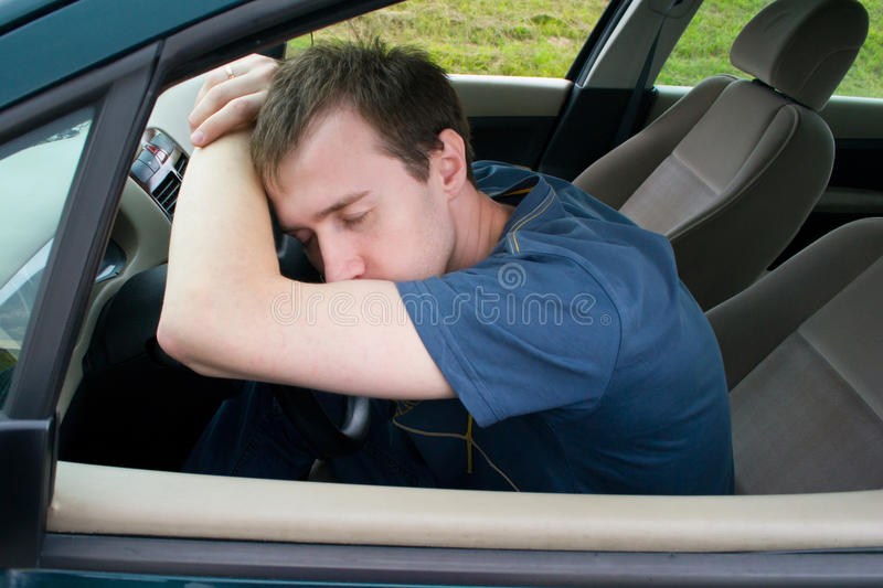 The man sleeps in the car stock image