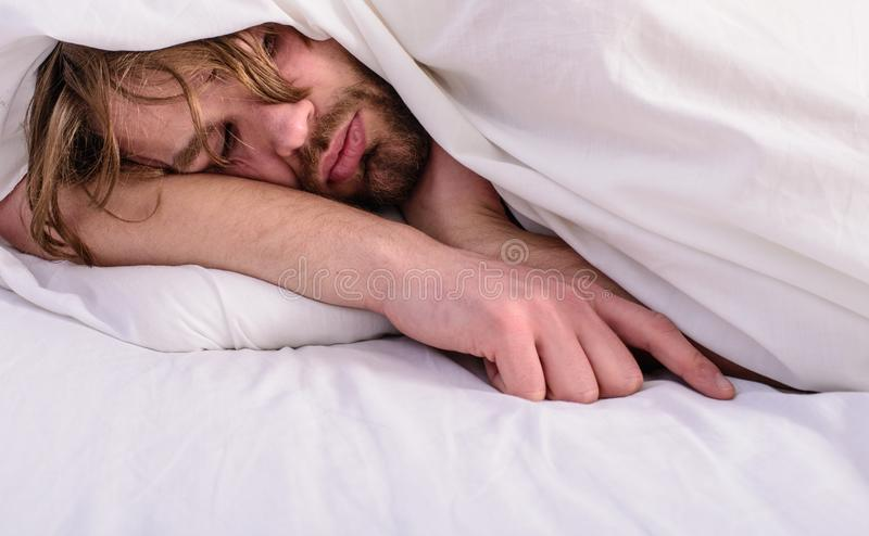Man sleepy drowsy unshaven bearded face covered with blanket having rest. Guy lay under white bedclothes. Fresh. Bedclothes concept. Man unshaven handsome royalty free stock photos