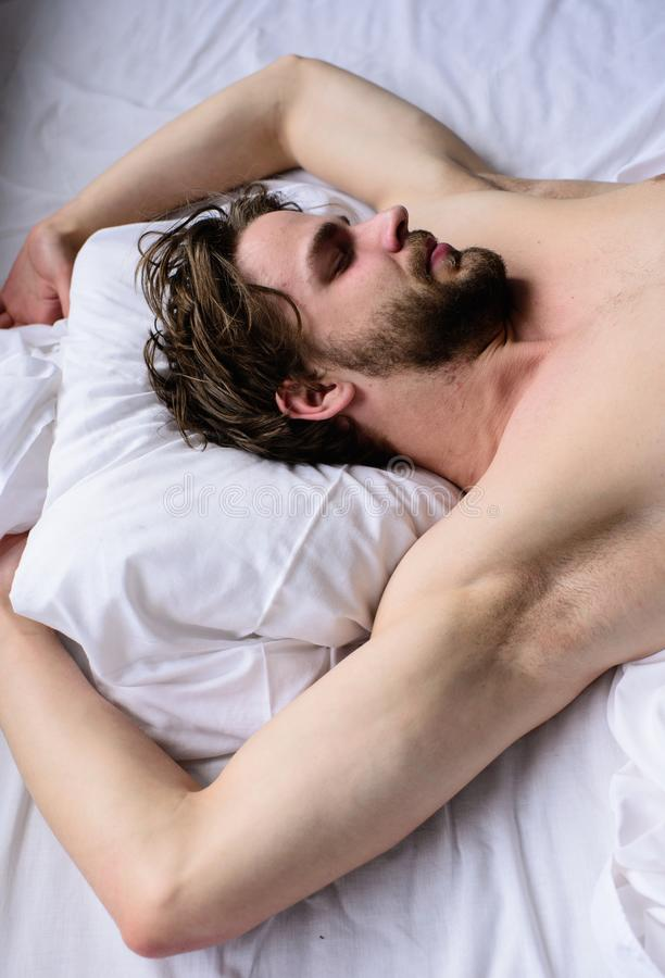 Man sleepy unshaven bearded face sleep has rest. Pleasant dream concept. Guy macho lay white bedclothes. Let your. Body feel comfortable. Man unshaven handsome royalty free stock images
