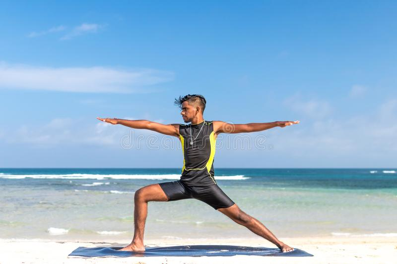 Man in Sleeveless Wet Suit Doing Some Aerobics at the Beach royalty free stock image