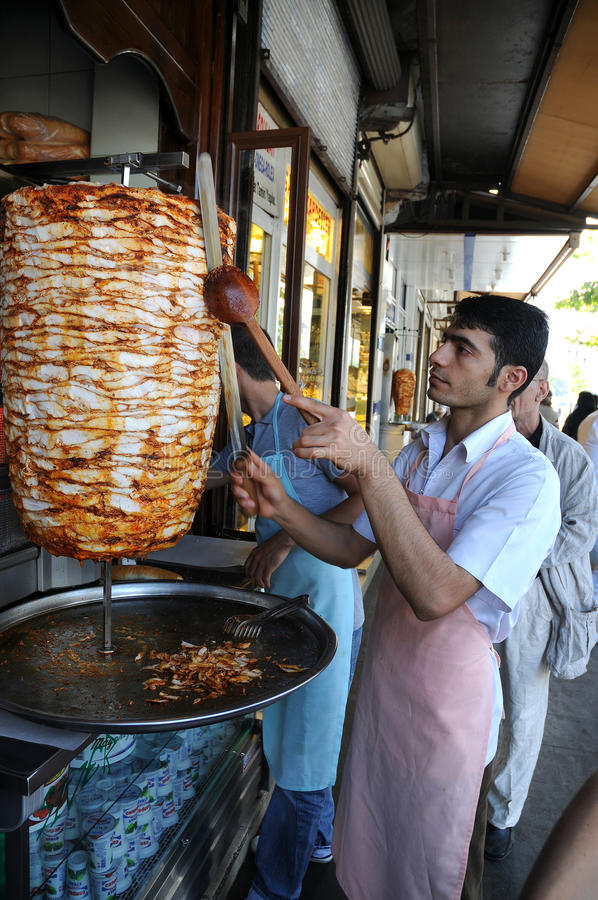 Man slices doner kebab. Doner kebab is a turkish dish made of meat cooked on a vertical rotisserie, normally lamb but sometimes beef, or chicken. A man slices