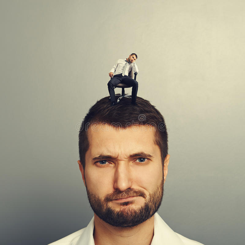 Man with small bored man. Portrait of dissatisfied man with small bored man on the head stock image
