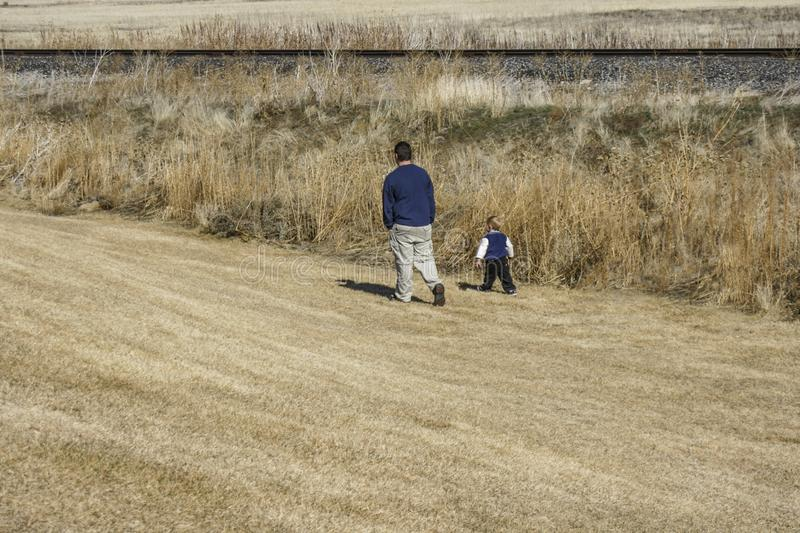 Man and small boy walking in a field next to some railroad tracks stock photos