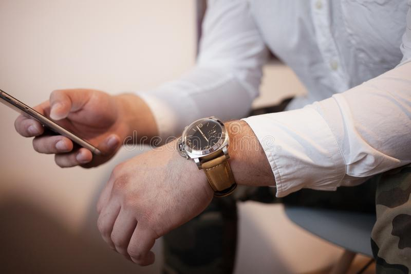 A man with smart phone in a relaxed pose in a white shirt is typing sms psychology and negotiation concept stock photography