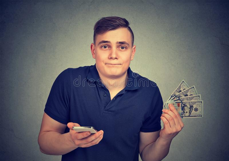 Man with smart phone throwing away cash dollar bills. Isolated on gray wall background stock photo